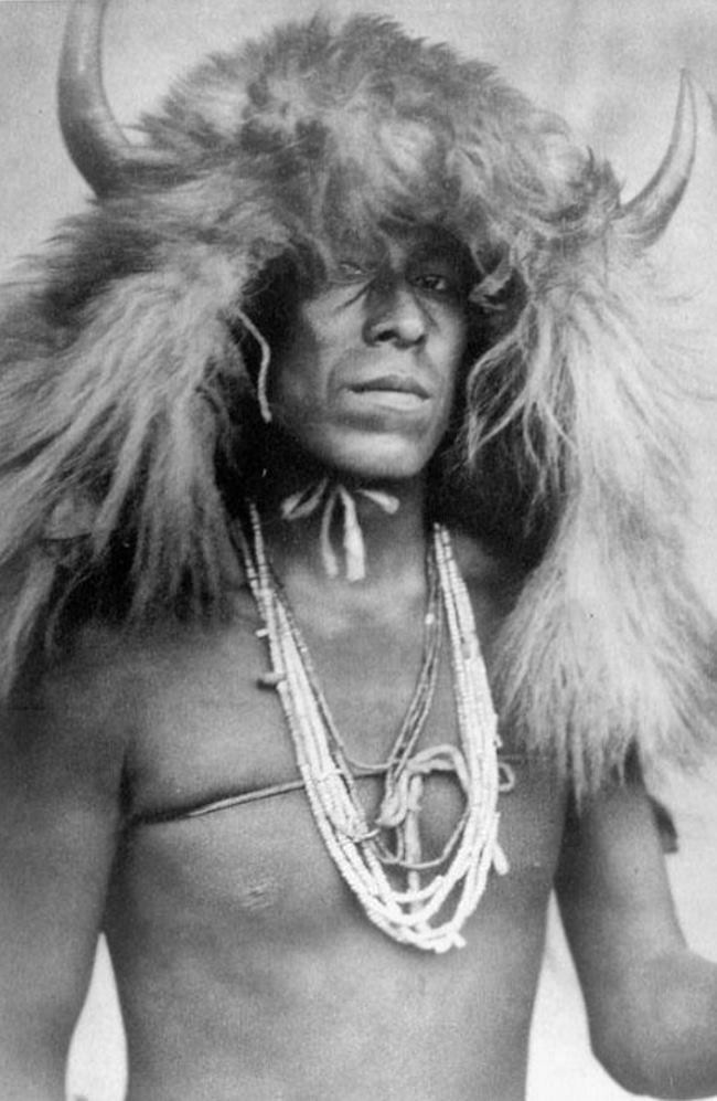 Индеец-сиу (sioux, относятся к языковой семье сиу (siouan) в головном уборе с рогами буйвола (buffalo headdresses). Со старинной фотографии.