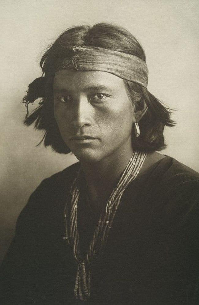 Инддец из племени навахо (navajo) в тканевой головной повязке. Со старинной фотографии. Племена навахо относятся к атабаскской (athabascan) языковой семье. В настоящее время резервация нации навахо, где проживает ок. 174 тыс. ( на 2015 г.) навахо (что составляет 58,34 % всех индейцев навахо в США) – является крупнейшей индейской резервацией в Соединенных Штатах Америки. Резервация находится на стыке четырех штатов США: Аризоны, Юты, Колорадо и Нью-Мексико, и управляется местным индейским самоуправлением, включающем парламент навахо - Совет нации навахо (Navajo Nation Council).