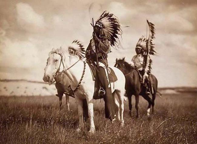 Вожди западных, иначе равнинных сиу (sioux) в головных уборах индейского воина warbonnet и на лошадях. Фотография сделана в 1905 г. знаменитым американским фотографом Эдвардом Кертисом (Edward S. Curtis, годы жизни: 1868-1952). Сиу относятся относятся к языковой семье сиу (siouan).