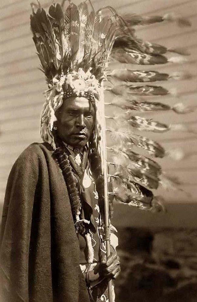 Воин племени пикани (piegan), - племени, относящегося к народу черноногих (blackfeet, иначе blackfoot, или фр. pieds-noirs (пье-нуар), в головном уборе индейского воина warbonnet. Фотография сделана в 1910 г. знаменитым американским фотографом Эдвардом Кертисом (Edward S. Curtis, годы жизни: 1868-1952). Черноногие относятся к алгонкинской (algonquian) языковой семье.